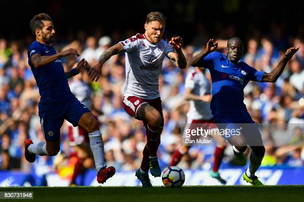 Jeff Hendrick of Burnley is tackled by Cesc Fabregas of Chelsea and N'Golo Kante of Chelsea during the Premier League match between Chelsea and...