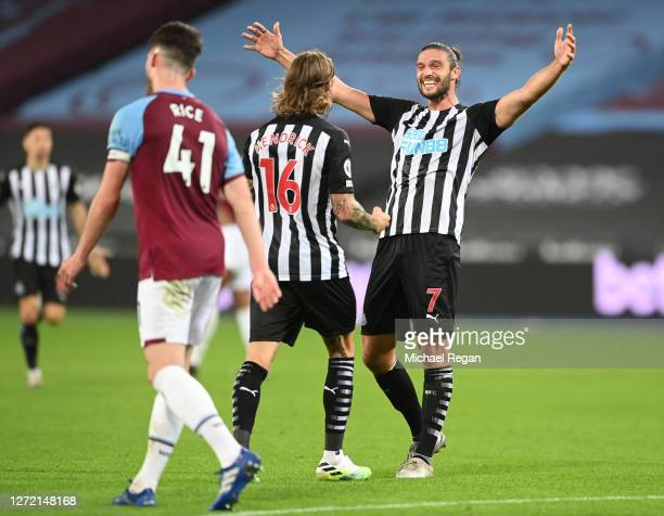Jeff Hendrick of Newcastle United celebrates with teammate Andy Carroll after scoring his team's second goal during the Premier League match between...
