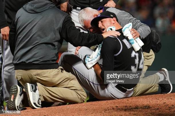 Jeff Hoffman of the Colorado Rockies reacts to being hit in the leg with a line drive during the fourth inning against the San Francisco Giants at...