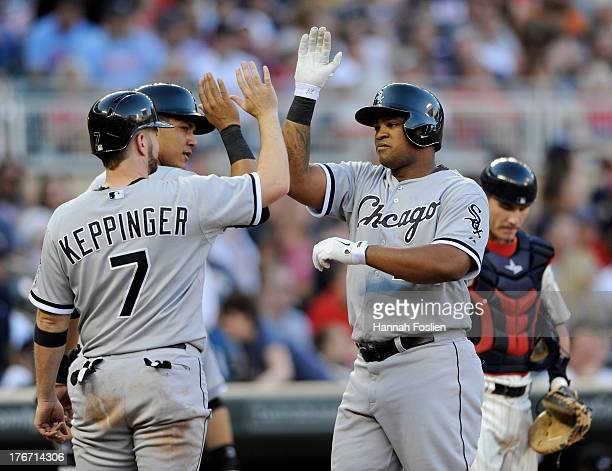 Jeff Keppinger and Avisail Garcia of the Chicago White Sox congratulate teammate Dayan Viciedo on a three run home run as Chris Herrmann of the...