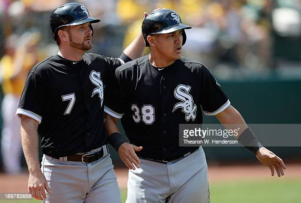 Jeff Keppinger and Hector Gimenez of the Chicago White Sox celebrate after they both scored on a Alejando De Aza two run single during the seventh...