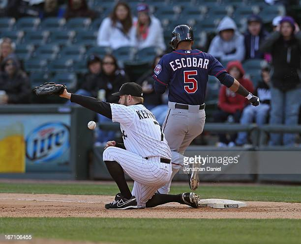 Jeff Keppinger of the Chicago White Sox misses a throw for an error on teammate Alexei Ramirez as Eduardo Escobar of the Minnesota Twins crosses...