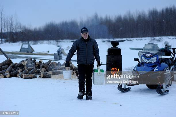 Jeff King carries coolers of hot water back to his team at the Nikolai checkpoint during the 2014 Iditarod Trail Sled Dog Race on Tuesday March 4 in...