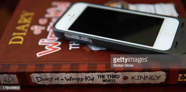 Jeff Kinney author of Diary of a Wimpy Kid has a copy of one of his books and an iPhone on a desk in his work area He has a small house next to his...