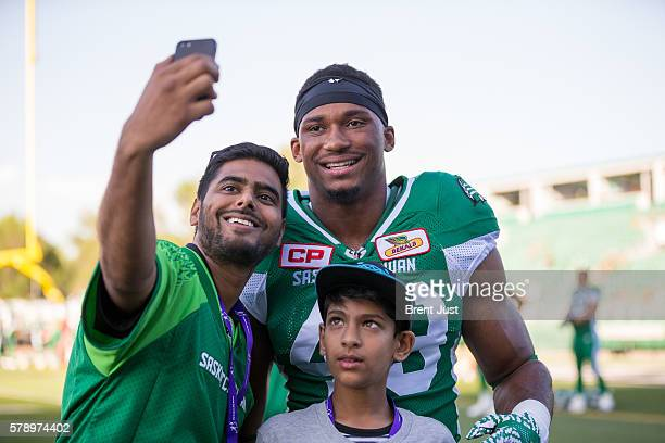 Jeff Knox Jr #49 of the Saskatchewan Roughriders pauses to take a picture with some fans before the pregame warmup for the game between the Ottawa...