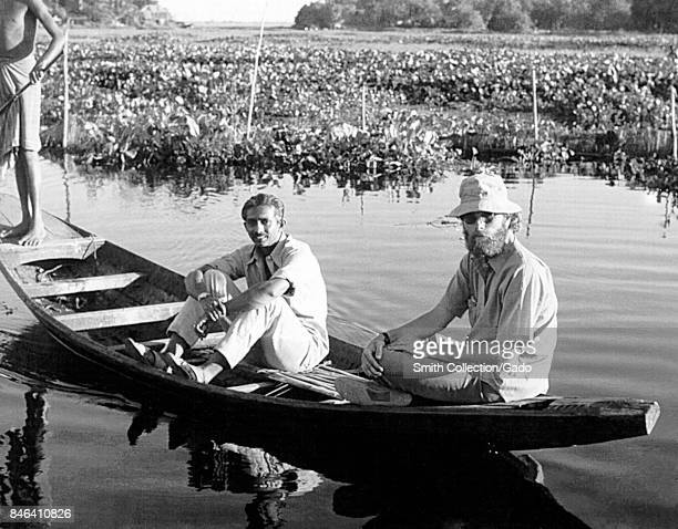 Jeff Koplan MD MPH with another man and a native villager in a small boat among marshland during a smallpox eradication effort Bangladesh 1970 Image...