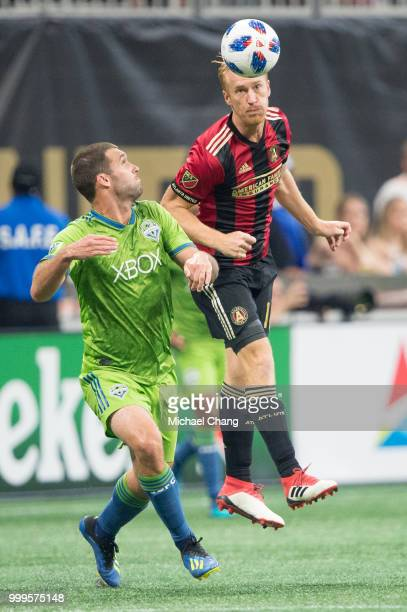 Jeff Larentowicz of Atlanta United heads the ball by Will Bruin of Seattle Sounders FC 2 during the game at MercedesBenz Stadium on July 15 2018 in...