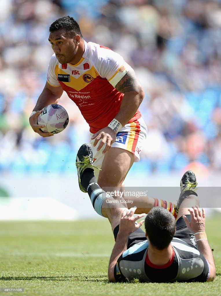 Jeff Lima of Catalan Dragons knocks over Matt Cook of London Broncos on his way to scoring during the Super League match between London Broncos and Catalan Dragons at Etihad Stadium on May 17, 2014 in Manchester, England.