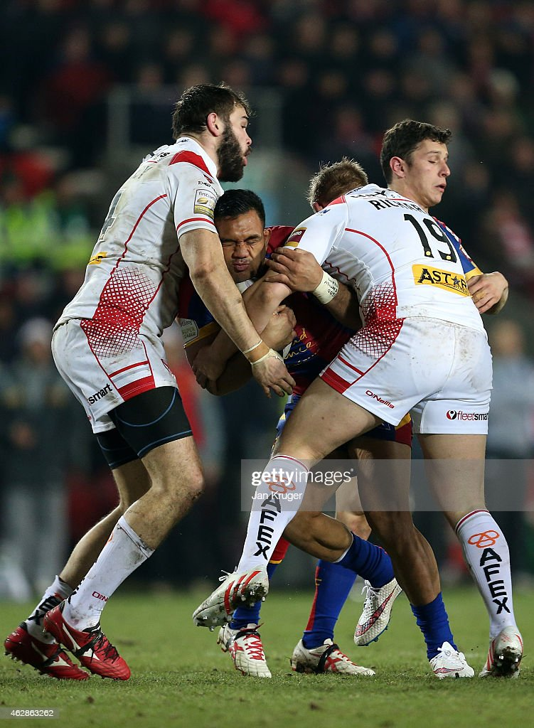 Jeff Lima of Catalans Dragons is tackled by Josh Jones and Alex Walmsley of St Helens during the First Utility Super League match between St Helens and Catalans Dragons at Langtree Park on February 6, 2015 in St Helens, England.
