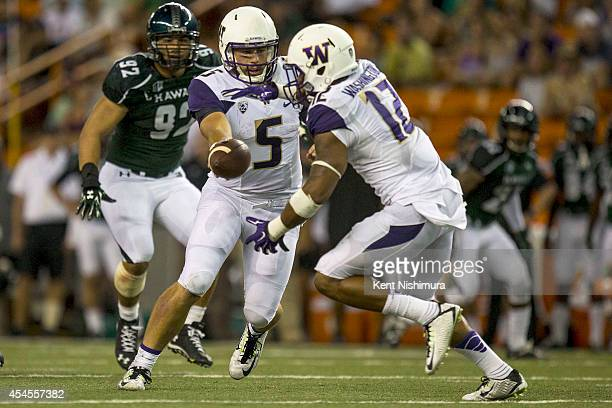 Jeff Lindquist hands the ball off to Dwayne Washington of the Washington Huskies during a college football game between the Washington Huskies and...