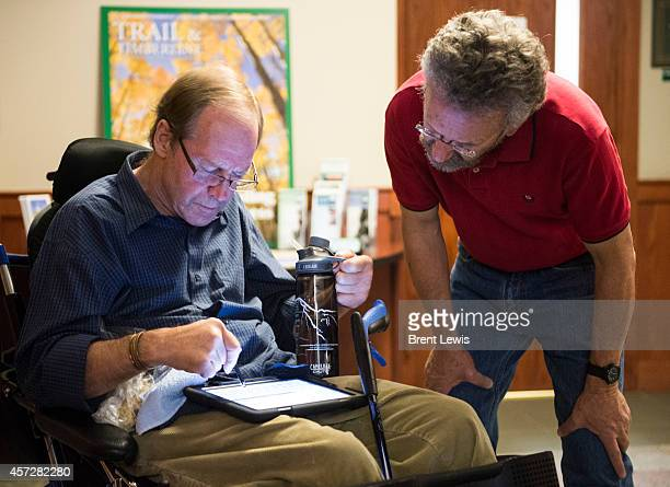 Jeff Lowe types a message to John Scheunemann before the start of the Ouroy Ice Park Road Show event Wednesday October 15 2014 at the American...