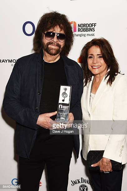 Jeff Lynne and Camelia Kath pose with the Icon Award during the Nordoff Robbins O2 Silver Clef Awards on July 1 2016 in London United Kingdom