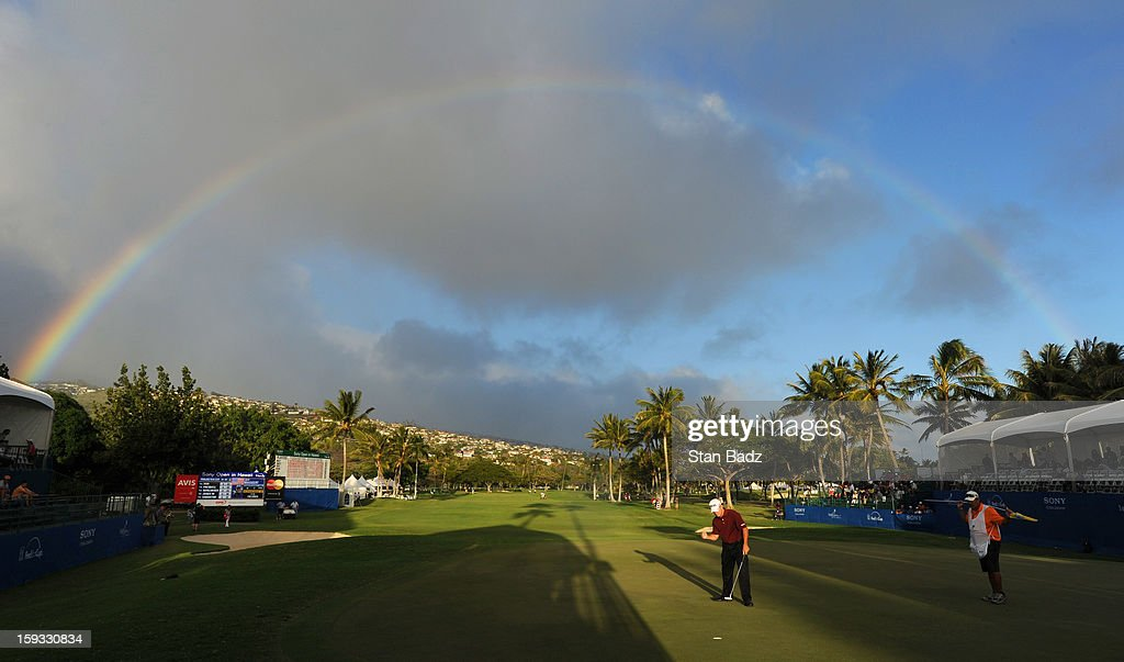 Jeff Maggert reacts to his birdie putt on the 18th green as a rainbow appears during the second round of the Sony Open in Hawaii at Waialae Country Club on January 11, 2013 in Honolulu, Hawaii.
