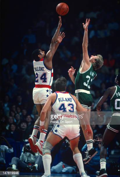 Jeff Malone of the Washington Bullets shoots over Larry Bird of the Boston Celtics during an NBA basketball game circa 1983 at the Capital Centre in...