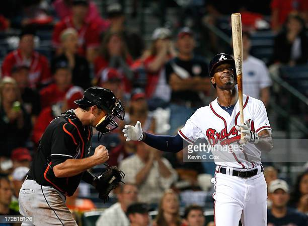 Jeff Mathis of the Miami Marlins celebrates their 43 win as BJ Upton of the Atlanta Braves reacts to striking out to end the ninth inning at Turner...