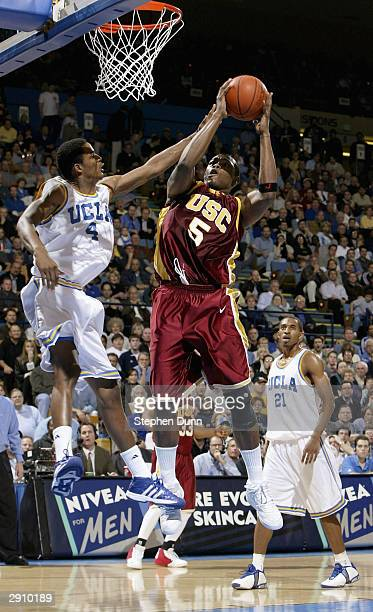 Jeff McMillan of the USC Trojans goes to the basket against Trevor Ariza of the UCLA Bruins January 28 2004 at Pauley Pavillion in Westwood California