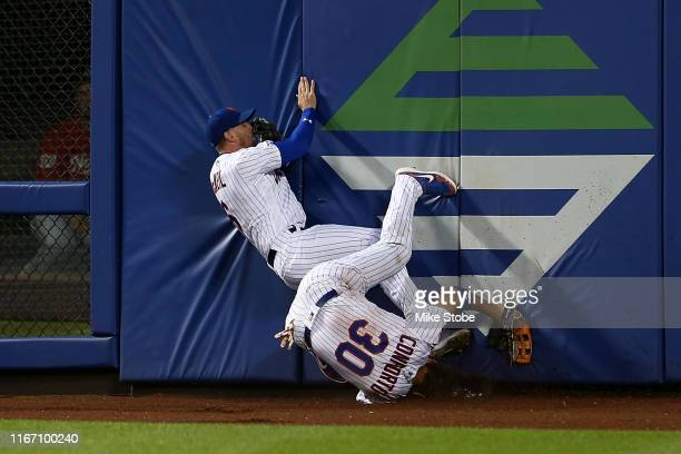 Jeff McNeil and Michael Conforto of the New York Mets collide chasing after Anthony Rendon of the Washington Nationals triples in the fourth inning...