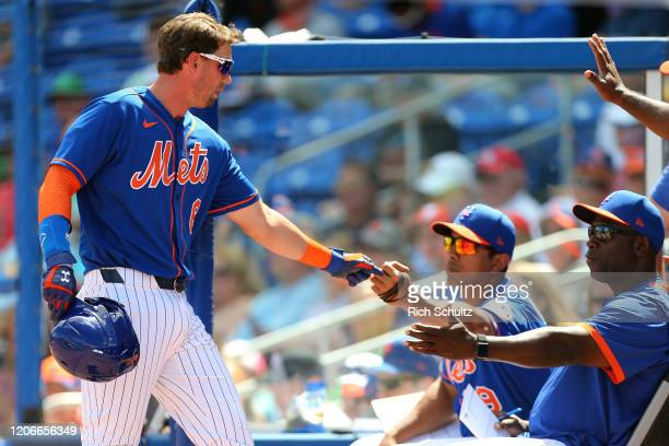 Jeff McNeil of the New York Mets is congratulated by manager Luis Rojas and bench coach Hensley Meulens after scoring on a single by JD Davis against...