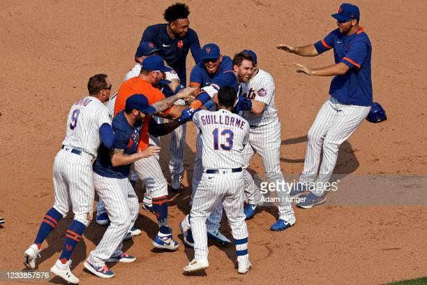 Jeff McNeil of the New York Mets is congratulated by teammates after hitting a walk-off 2-RBI single in the eighth inning against the Milwaukee...