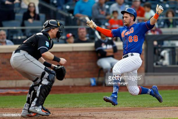 Jeff McNeil of the New York Mets scores a run past Chad Wallach of the Miami Marlins during the fourth inning at Citi Field on September 30 2018 in...