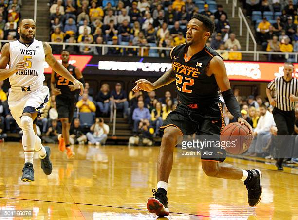 Jeff Newberry of the Oklahoma State Cowboys drives the ball down court against Jaysean Paige of the West Virginia Mountaineer during the game at the...