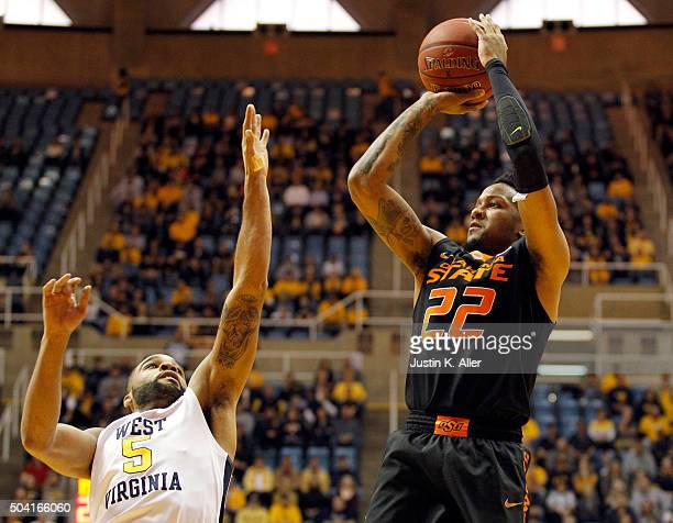 Jeff Newberry of the Oklahoma State Cowboys pulls up for a shot against Jaysean Paige of the West Virginia Mountaineers during the game at the WVU...