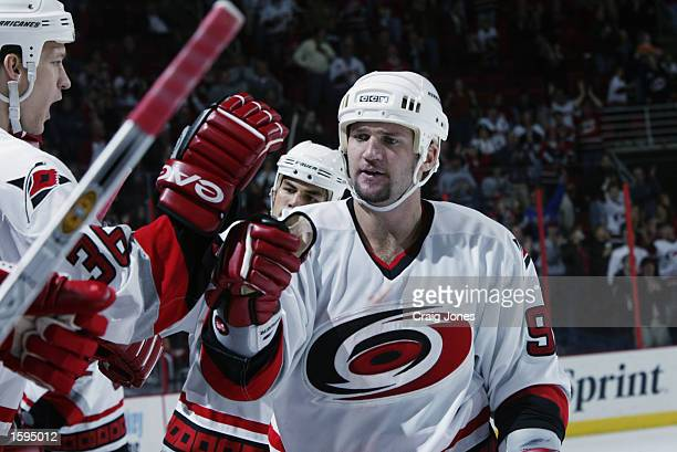 Jeff O'Neill of the Carolina Hurricanes is congratulated after scoring the tying goal against the New York Islanders during the NHL game on October...