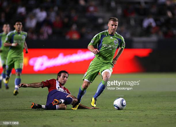 Jeff Parke of Seattle Sounders FC paces the ball on the attack as Alan Gordon of Chivas USA slides in for the tackle in the second half of their MLS...
