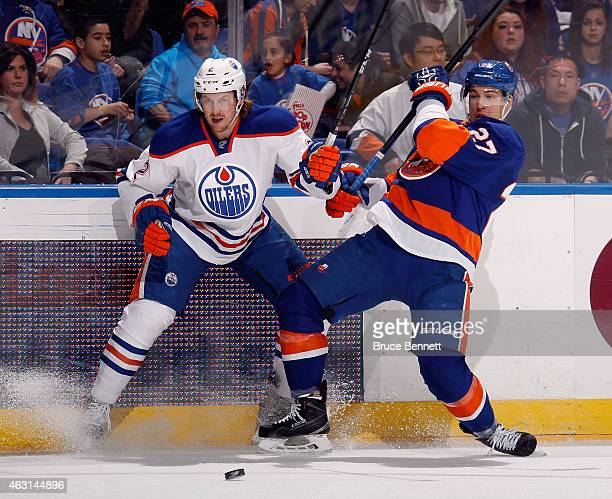 Jeff Petry of the Edmonton Oilers and Brian Strait of the New York Islanders battle for the puck during the first period at the Nassau Veterans...