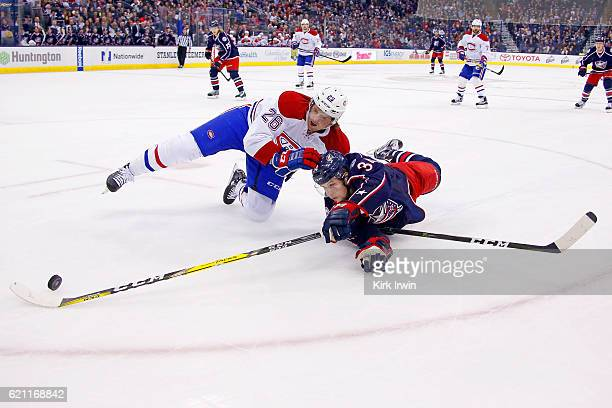 Jeff Petry of the Montreal Canadiens and Josh Anderson of the Columbus Blue Jackets lose their footing while battling for control of the puck during...