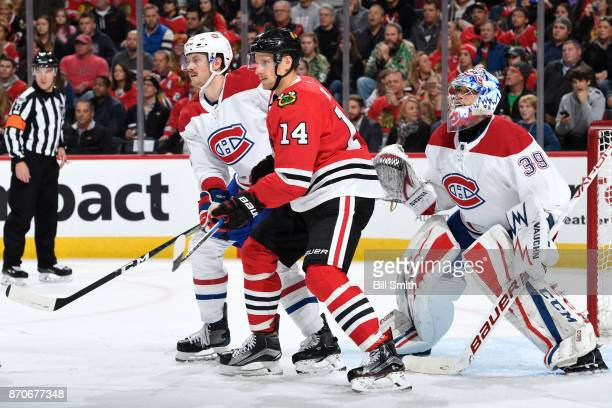 Jeff Petry of the Montreal Canadiens and Richard Panik of the Chicago Blackhawks wait in position in front of goalie Charlie Lindgren in the first...