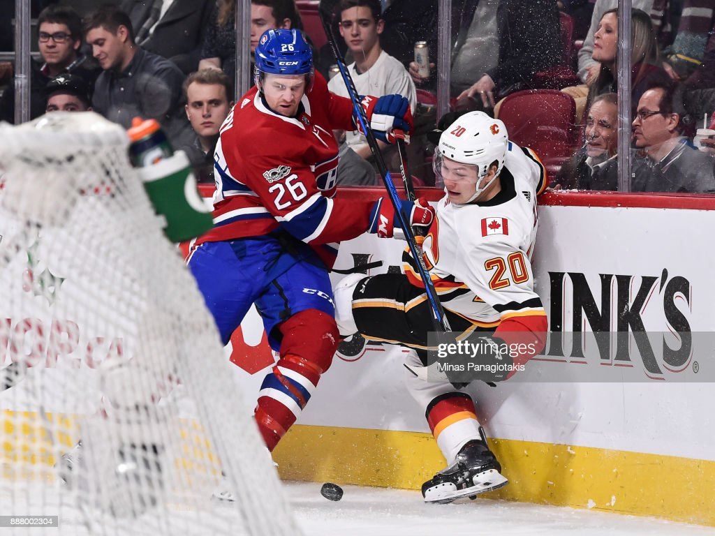 Jeff Petry #26 of the Montreal Canadiens takes down Curtis Lazar #20 of the Calgary Flames near the boards during the NHL game at the Bell Centre on December 7, 2017 in Montreal, Quebec, Canada. The Calgary Flames defeated the Montreal Canadiens 3-2 in overtime.