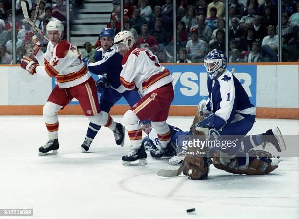 Jeff Reese and Al Iafrate of the Toronto Maple Leafs skates against Jim Peplinski and Lanny McDonald of the Calgary Flames during NHL game action on...