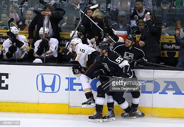 Jeff Schultz and Kyle Clifford of the Los Angeles Kings check Corey Perry of the Anaheim Ducks along the side boards during the second period of Game...