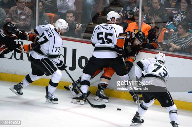 Jeff Schultz of the Los Angeles Kings checks Nick Bonino of the Anaheim Ducks into the boards as Jeff Carter and Tyler Toffoli of the Los Angeles...