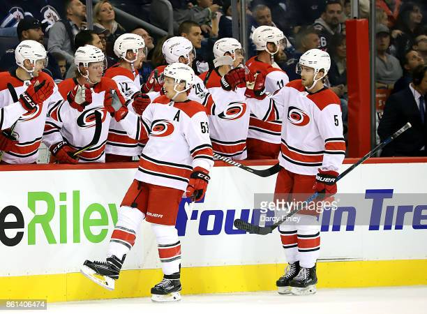 Jeff Skinner and Noah Hanifin of the Carolina Hurricanes celebrate a first period goal against the Winnipeg Jets with teammates at the bench at the...