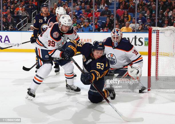 Jeff Skinner of the Buffalo Sabres dives for the puck as Alex Chiasson and Mikko Koskinen of the Edmonton Oilers defend during an NHL game on March 4...