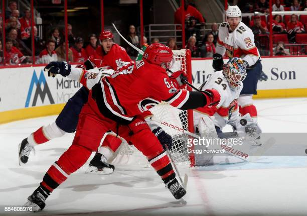 Jeff Skinner of the Carolina Hurricanes backhands the puck on the crease as James Reimer of the Florida Panthers makes the save during an NHL game on...