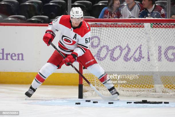 Jeff Skinner of the Carolina Hurricanes clears pucks from the goal during warm ups prior to the game against the Colorado Avalanche at the Pepsi...
