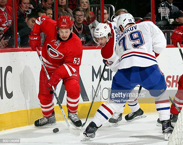 Jeff Skinner of the Carolina Hurricanes maneuvers the puck around Sven Andrighetto and Andrei Markov of the Montreal Canadiens during an NHL game at...