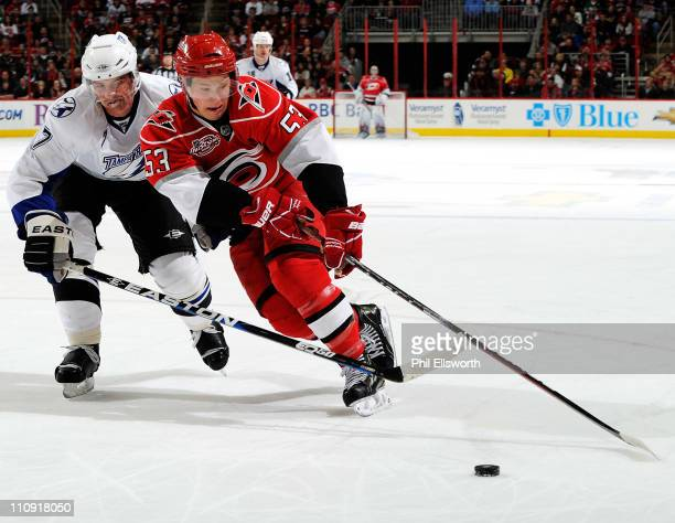 Jeff Skinner of the Carolina Hurricanes moves the puck around Brett Clark of the Tampa Bay Lightning during an NHL game on March 26 2011 at RBC...