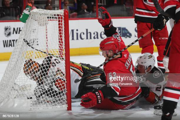 Jeff Skinner of the Carolina Hurricanes scores on Ryan Miller of the Anaheim Ducks as both go down in the crease during an NHL game on October 29...