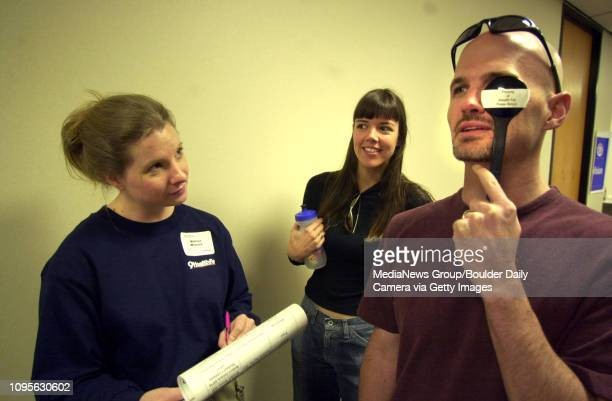 Jeff Staron of Boulder calls out the letters on the standard vision test chart while his friend Rebecca Koepke attempts to check on his accuracy at...