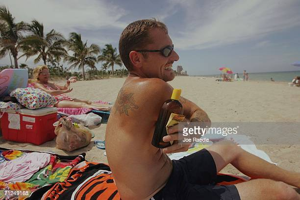 Jeff Stidham puts sun tan oil on his back during a visit to the beach June 20 2006 in Fort Lauderdale Florida Recent studies have shown that the best...