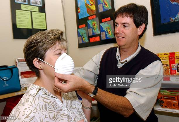 Jeff Tateosian shows Paula Krzeninski how to wear a dust mask October 16 2001 at Earthshakes in Burlingame CA Since the terrorist attacks in New York...