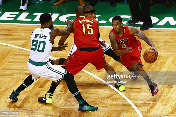 Jeff Teague of the Atlanta Hawks drives around Al Horford with pressure from Amir Johnson of the Boston Celtics during the first quarter of Game Six...