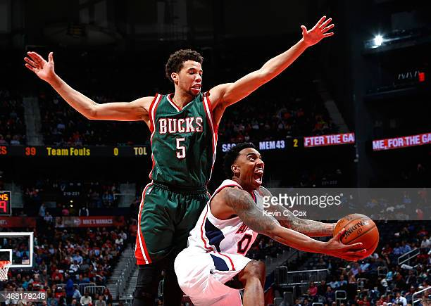 Jeff Teague of the Atlanta Hawks drives under Michael CarterWilliams of the Milwaukee Bucks at Philips Arena on March 30 2015 in Atlanta Georgia NOTE...