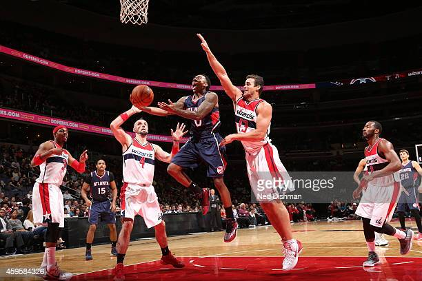 Jeff Teague of the Atlanta Hawks goes to the basket against Kris Humphries of the Washington Wizards on November 25 2014 at the Verizon Center in...