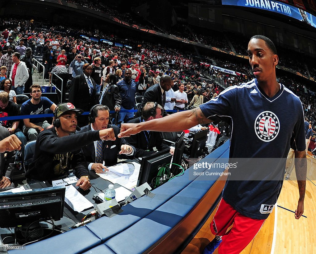 Jeff Teague #0 of the Atlanta Hawks high fives rapper T.I. before the game against the Miami Heat at Philips Arena on November 9, 2012 in Atlanta, Georgia.