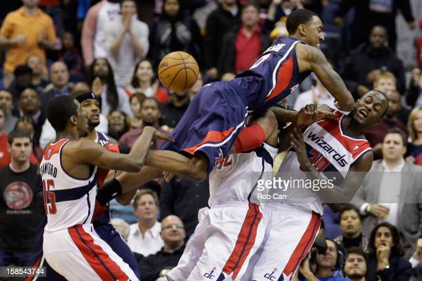 Jeff Teague of the Atlanta Hawks is called for an offensive foul while going to the basket against Jordan Crawford Nenê and Earl Barron of the...